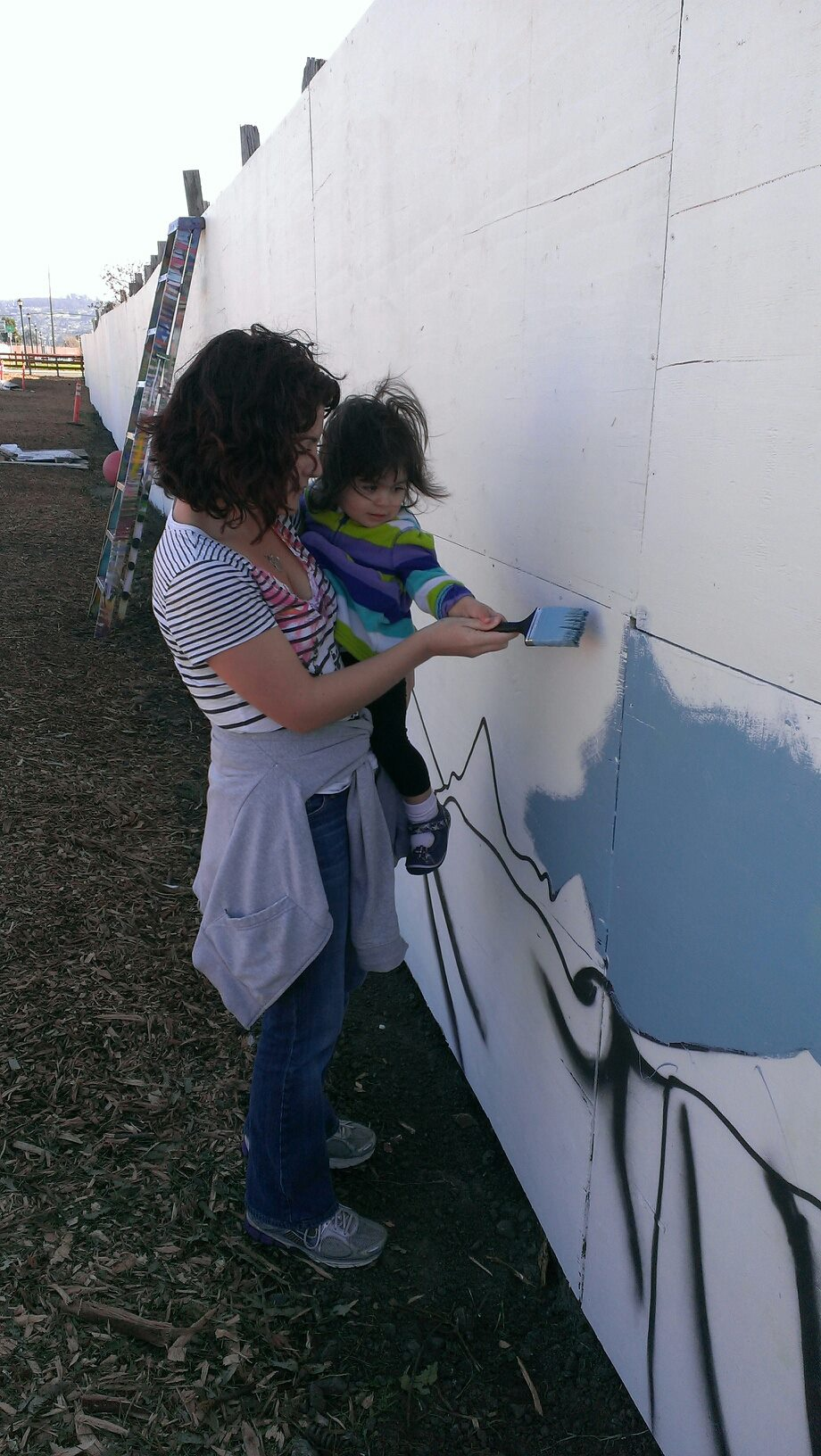 Calisi Rodríguez and her daughter help paint a mural at the community gardens on the Ohlone Greenway for the MLK Day of Service in Richmond, Calif. Courtesy Photo