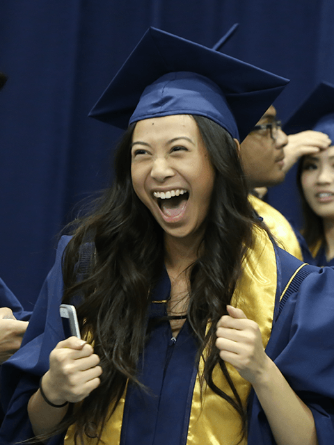 A student celebrates during the College of Biological Sciences commencement ceremony