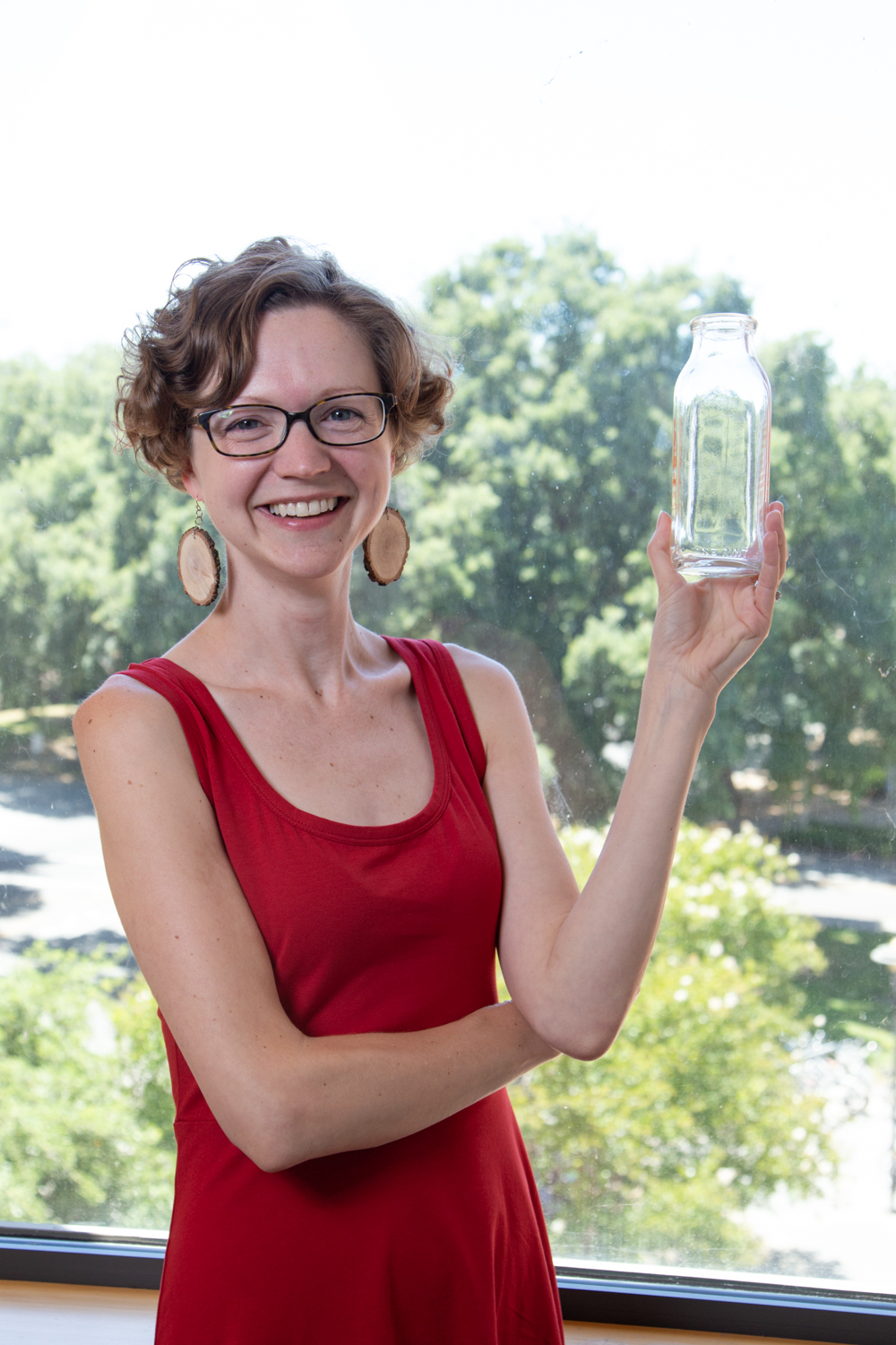 Ori-McKenney stands with a milk bottle, which used to be used to house flies in the early days of fly studies. David Slipher/UC Davis