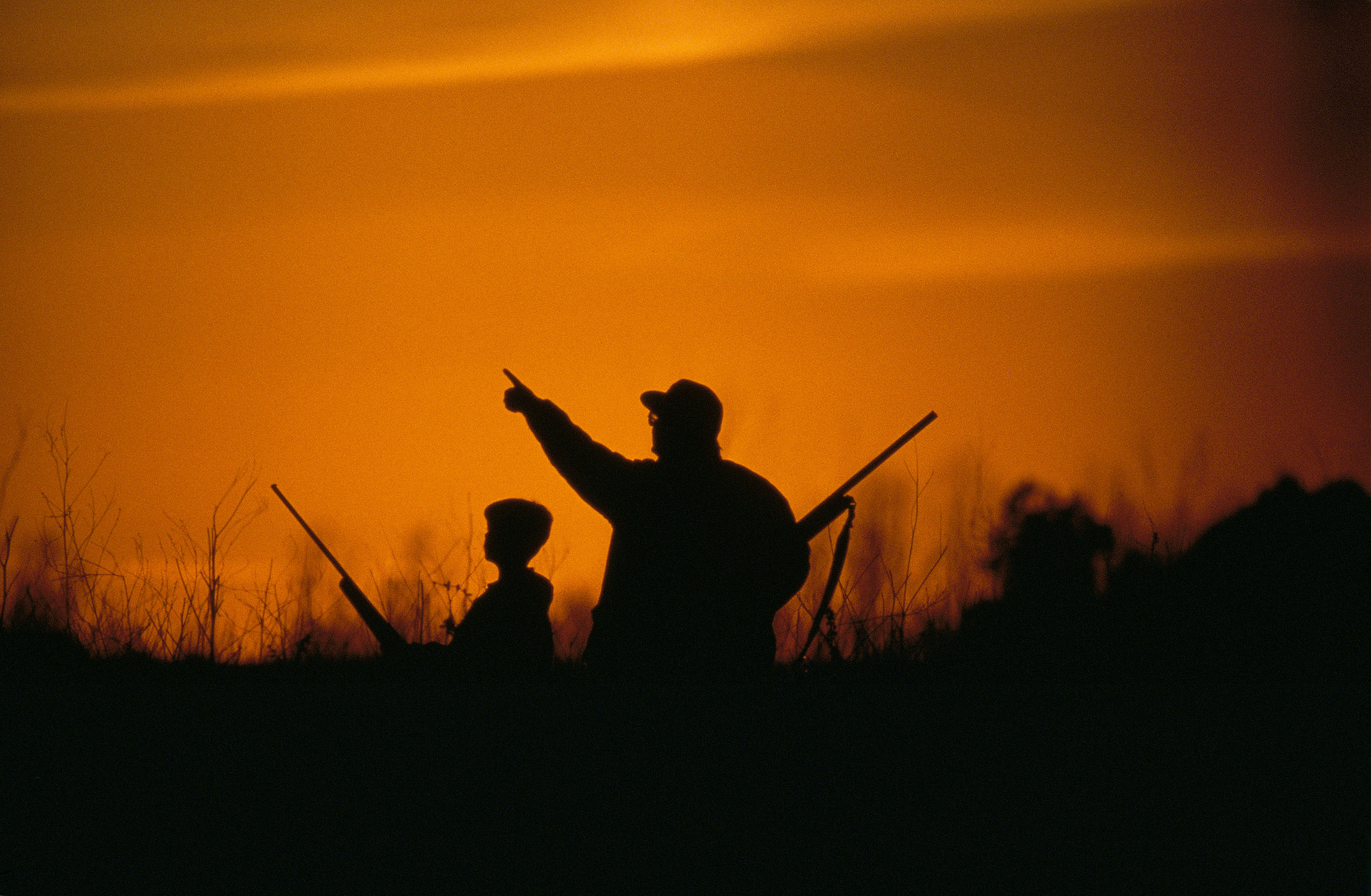 Image of two hunters against a sunset-colored sky. United States FIsh and Wildlife Service