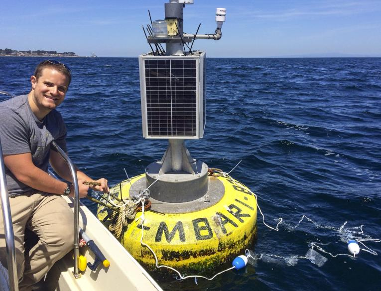 UC Davis graduate student Matthew Savoca sits beside a research buoy as part of his marine plastic research into why seabirds eat plastic. Photo: Courtesy Matthew Savoca