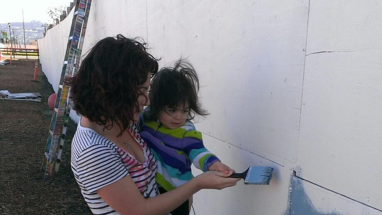 Rebecca M. Calisi Rodríguez and her daughter paint a mural at the community gardens on the Ohlone greenway for the MLK Day of Service