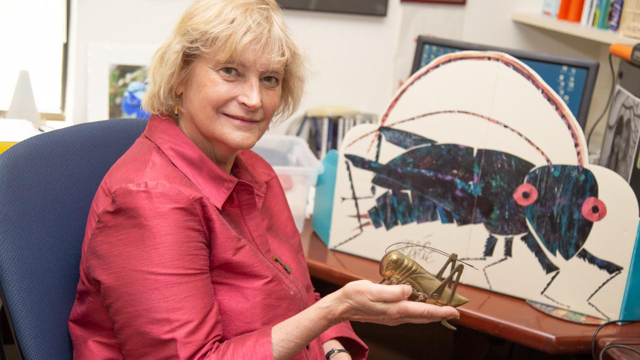 Ann Hedrick holds up a cricket statue in her office. David Slipher/UC Davis