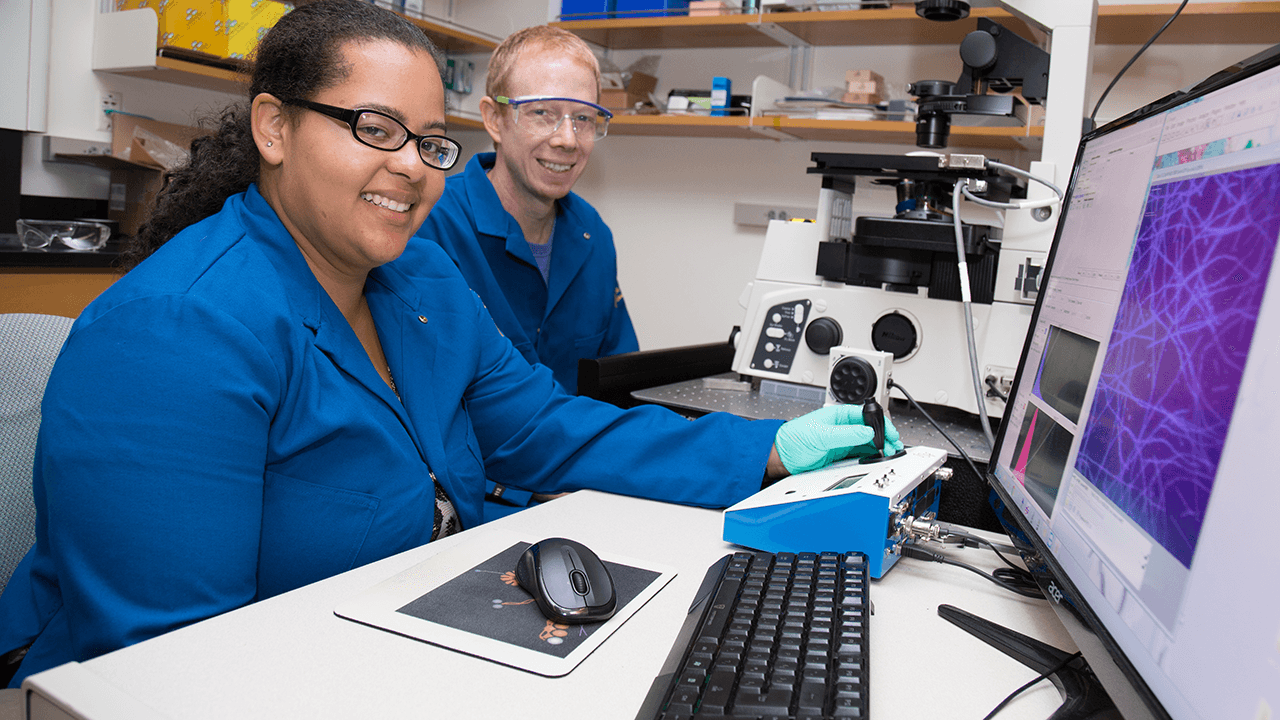An undergraduate researcher works in the lab with a faculty member