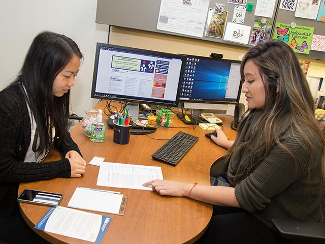 A student meets with a BASC advisor to plan her schedule.