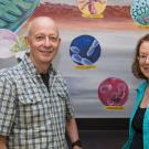 Professors Luca Comai and Michele Igo pose by a BIS 2A classroom mural. David Slipher/UC Davis