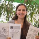 Young Scientist Program founder Briana Rocha-Gregg displays the group's new activity book Exciting Science by Cool Scientists!, a primer on model organisms. David Slipher/UC Davis