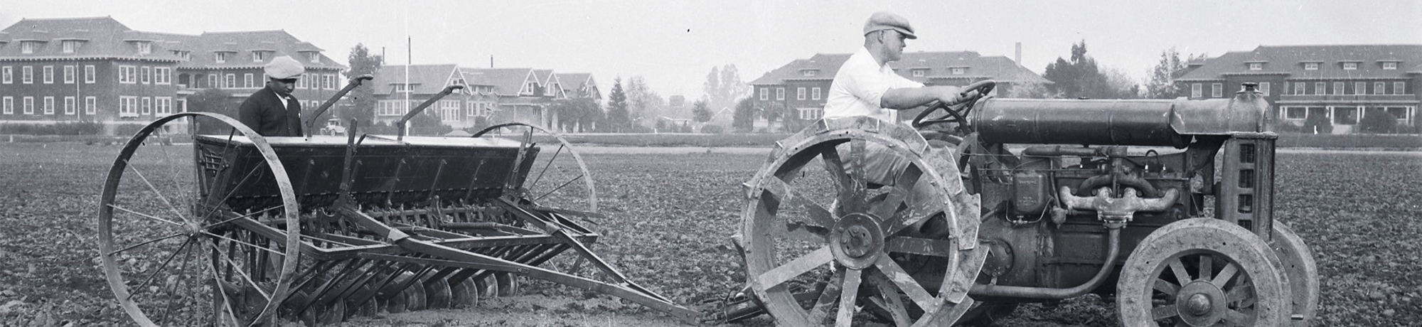 A tractor with a tiller attachment plows a field